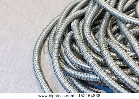 Flexible metal pipe on a background .