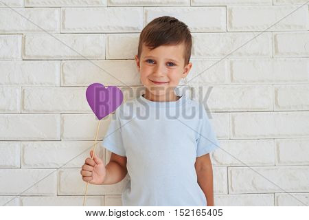 Handsome small boy with cornflower-blue eyes holding a paper heart ; standing against white wall