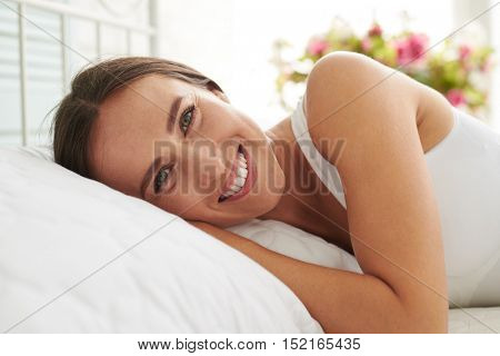 Close-up portrait of young Caucasian woman lying on the bed and smiling early in the morning