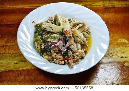 spicy stir fried squid with mushroom and basil leaf on dish