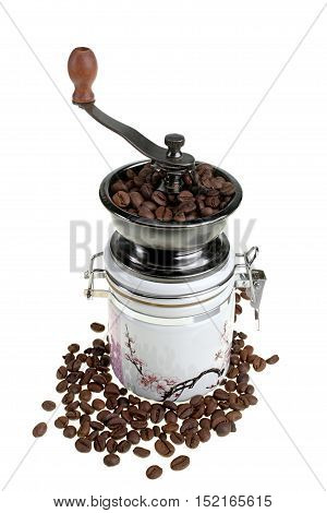 Manual coffee mill and scattered coffee beans isolated on white background with clipping path