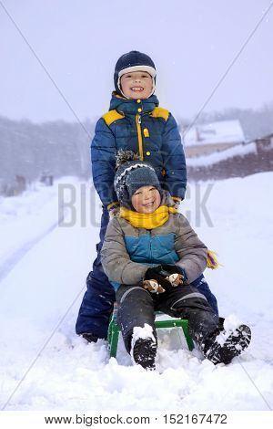two happy boys on sled in winter outdoors