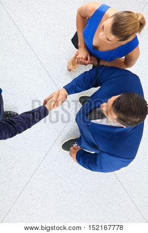 Business people shaking hands - topview on white background .