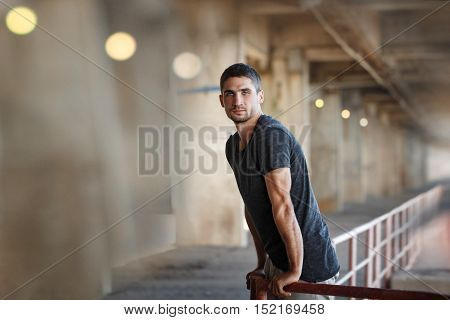 Men T-shirt of parkour in urban space. He climbs over the railing. Sport in the city. Movement is life.