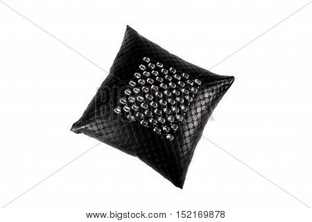 A luxurious black pillow made of leather and designed with glass beads on white studio background