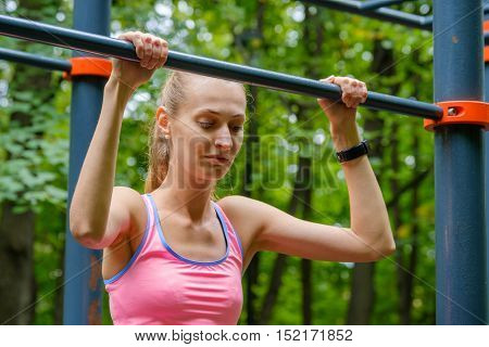 Young slim woman pulls on horizontal bar in a park