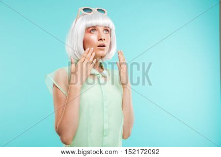 Amazed blonde young woman standing and looking up