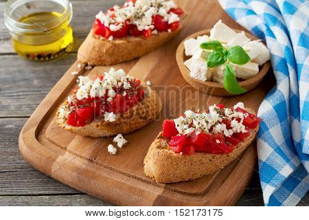 Bruschetta with tomatoes feta cheese and basil. Traditional Greek snack on wooden background. Selective focus.