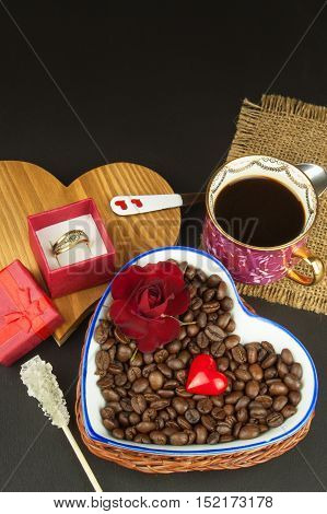 Romantic marriage proposal with good coffee. Romantic coffee. Marriage proposal. Coffee beans and a gold ring. Breakfast for lovers. Declaration of love on Valentine's Day.