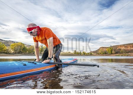 A senior male starting a workout on stand up paddleboard on a calm mountain lake