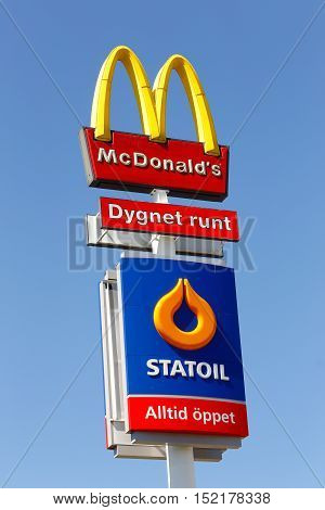 Eskilstuna, Sweden - June 14, 2014: Signs at Vasterleden for the fast food hamburger restaurant McDonalds and the Statoil service station isolated on blue sky. Both are newer closed.