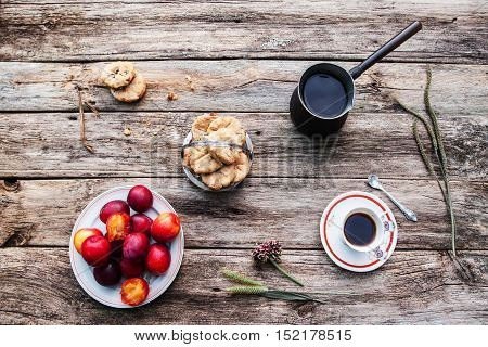 Fresh autumn breakfast for one, flat lay. Cup and pot of coffee with cookies and plums top view. Loneliness, rest from community concept