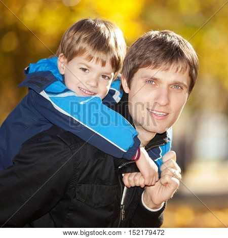 Happy father and his son walking in the autumn park. Beauty nature scene with colorful foliage background, yellow trees and leaves at fall season. Autumn outdoor lifestyle.