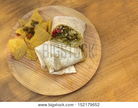 A photo of a tex-mex quesadilla, flatbread with rice, cheese, and peppers, served with nachos, traditional chips, on a wooden board, shot from above, with copyspace