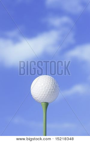 White golf ball on a green tee with blue sky.