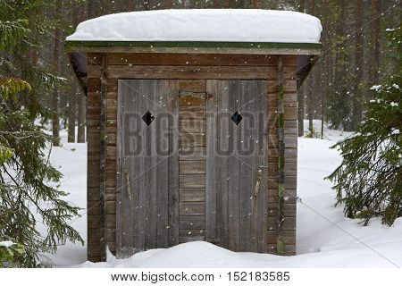 Open air toilet facility near by hiking trail in forest.