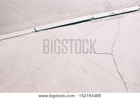 Sidewalk asphalt road with cracks. Old worn and cracked footpath close-up, gray urban background