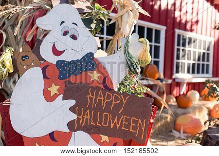 A ghost is holding a happy Halloween sign.