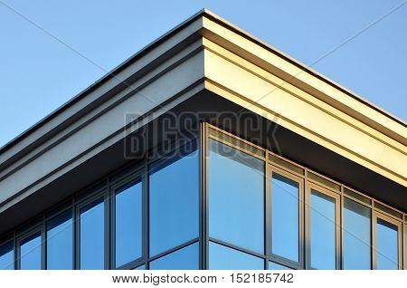 The angle of the top of the building with a cornice and a glass wall.