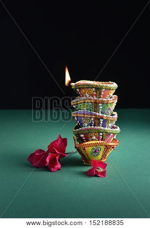 Diwali festive background and object. Many colorful handmade Diyas stacked on each other.
