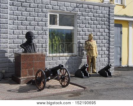 Two sculptures of the dictators of the Soviet Union are near the wall in the courtyard of the building