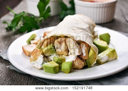 Wrap sandwich with chicken and avocado close up view