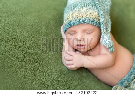 funny newborn baby in knitted hat sleeping with opened mouth on green blanket