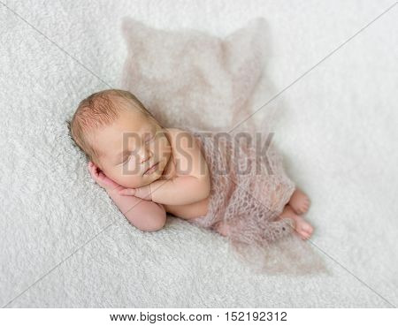 lovely smiling sleeping baby covered with light knitted shawl on white blanket