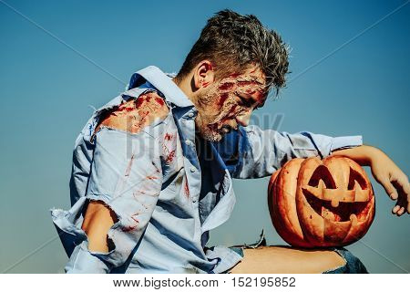 Handsome zombie man bloody young male or war soldier with wounds and red blood with Halloween pumpkin outdoors on blue sky