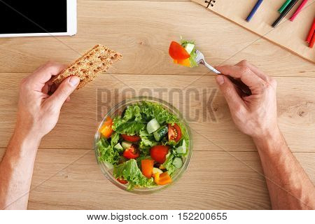 Business lunch at working place. Businessman in office. Hands of eating man. Healthy, diet food, vegetable salad with apple and juice. Cell phone and papers on desk. Top view, flat lay