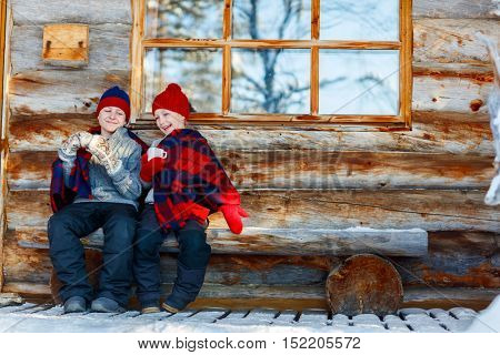 Kids outdoors on beautiful winter day drinking hot chocolate in front of log cabin vacation house