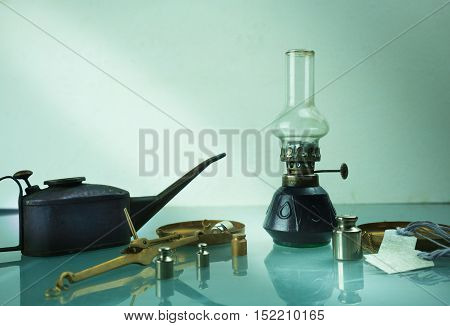 kerosene lamp, scales, weights, a watering can with oil