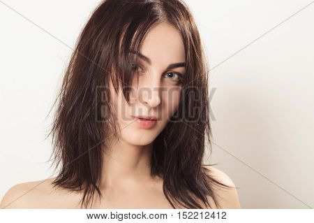 beautiful woman with fluffy hair looking at camera on white background