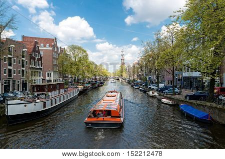 Westerkerk church with cruise ship in canal at Amsterdam Netherlands.Beautiful spring season in Amsterdam Netherlands.