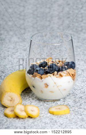 Dietetic breakfast - yoghurt with mueasli and huckleberries and banana
