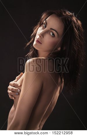 slim naked woman looking back on black background
