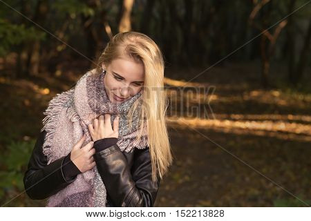 sad pensive blond girl in scarf outdoor