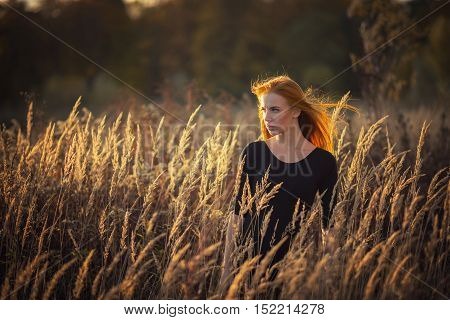 serious woman in dry grass at sunset