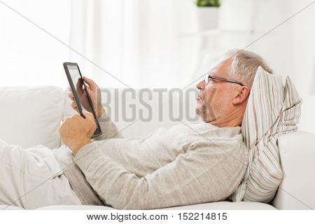 technology, people and lifestyle, distance learning concept - senior man with tablet pc computer lying on sofa at home