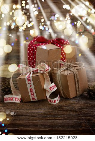 Pile of handmade gift boxes on wooden background with copy space glimming bokeh and light
