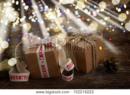 Two handmade gift boxes on wooden background glimming bokeh and light