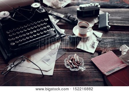Retro typewriter standin on a wooden table with different vintage things all around, such as retro photocamera, old glasses, pieces of paper, etc