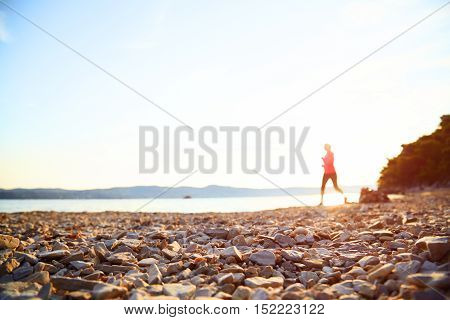 Silhouette of woman running on the rock beach. Happy jogger run and looking at the sea.