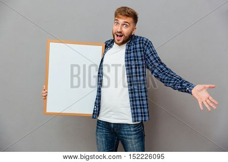 Cheerful bearded man holding blank board and shrugging shoulders isolated on a gray background