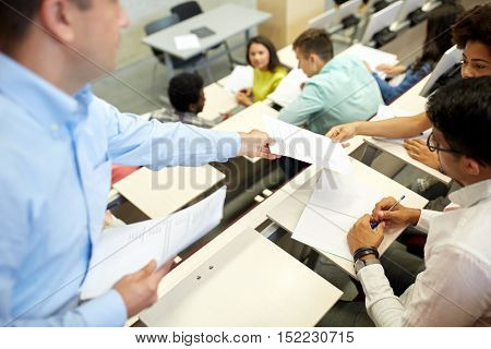 education, high school, university, learning and people concept - teacher giving exam tests to students at lecture hall