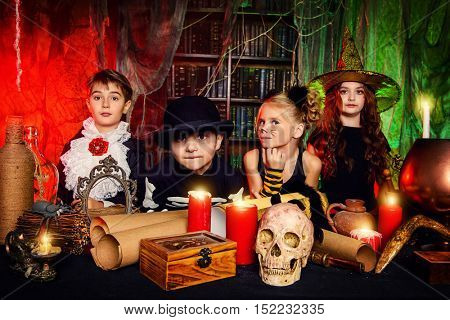 Group of funny children dressed in halloween costumes in a wizarding lair. Halloween party.