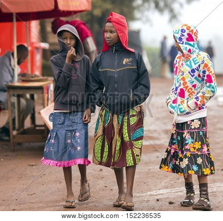 AFRICA, TANZANIA, MAY, 09, 2016 - Three african poorly dressed young girls on the streets in Arusha. Arusha is located below Mount Meru in the eastern branch of the Great Rift Valley and the capital of the Arusha Region.