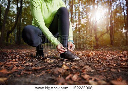 Unrecognizable Sportswoman Tying Shoes