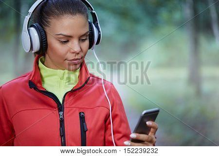 Sporstwoman Choosing Songs For Jogging