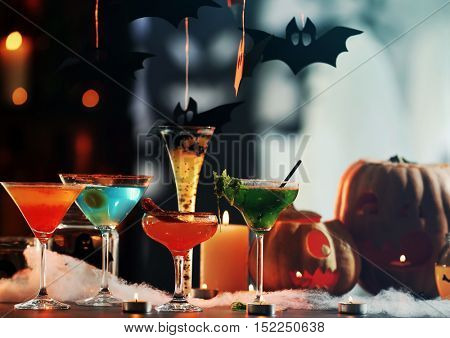 Colorful cocktails and decor for Halloween party, on blurred background